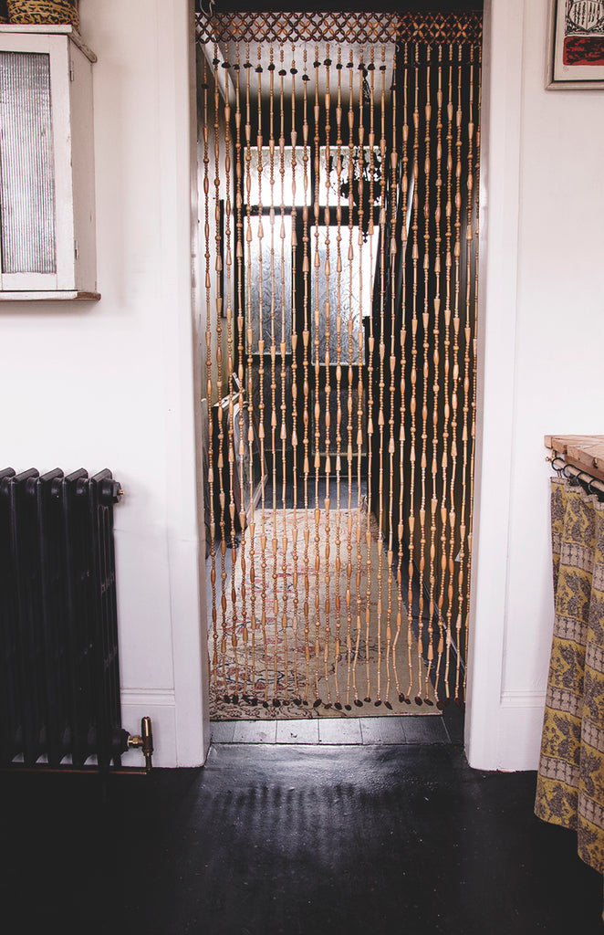 A vintage beaded curtain hanging in a doorway.