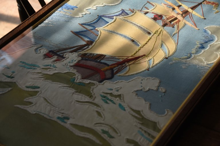 Original framed hand embroidery of a ship on the sea. Striking Colours, decorative interior design Bristol