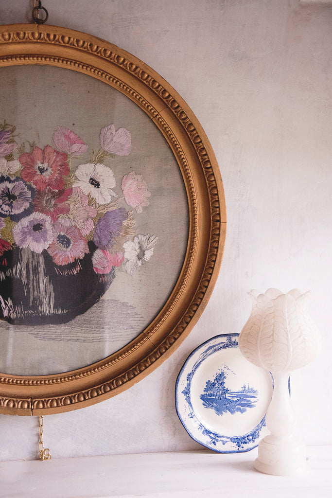 Antique embroidery in original gold circular frame against a distressed white wall