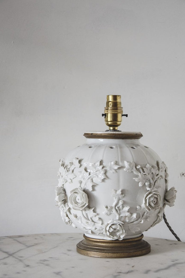 A vintage white porcelain table lamp, with delicate flower detailing. Bristol