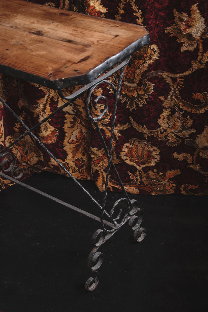 Simple vintage wooden side table with ornate iron work