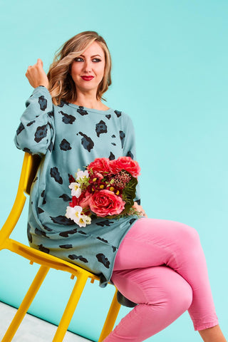 Woman sitting down in colourful clothing for chronic illnesses at Euphoria Boutique