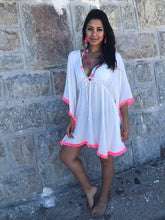 White beach dress with hot pink pom pom