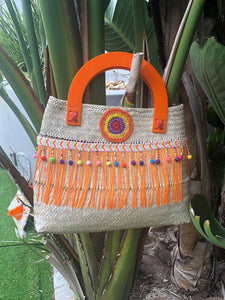 Hand woven basket bag with bright orange accents