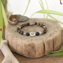 Tiger's eye, black onyx and lotus charm create this beautiful energetic healing crystal stretch bracelet.
