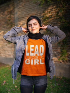 Girl with eyes closed wearing orange Lead Like A Girl Tshirt.