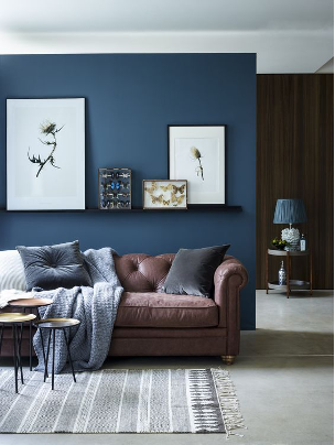 Blue accent wall with brown furniture