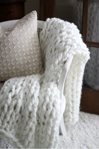 Draping a throw blanket over the arm of a chair or couch