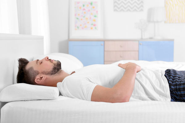 man sleeping with pillow on back