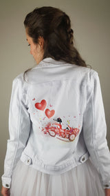 Red textile sticker with hearts and car ironed on denim jacket