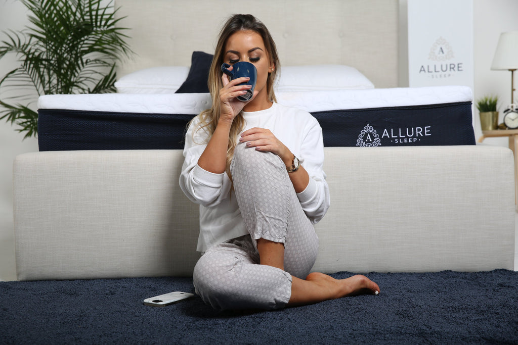 Woman sitting beside mattress drinking from a mug