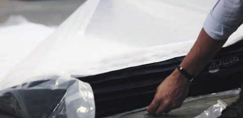 Hand unwrapping mattress to let air in