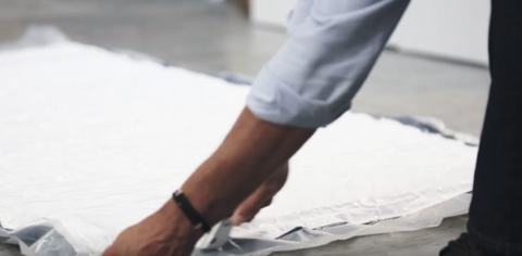 Hands Cutting Plastic Around Mattress