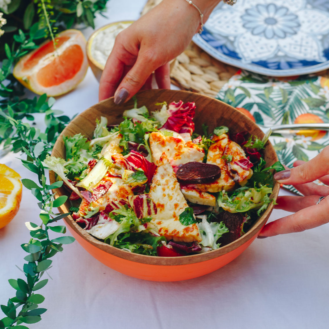 Sarah's Mediterranean Inspired Table with Indian Mango Wood Bowls and Orange Painted Outside with Leafy Salad - Talking Tables UK