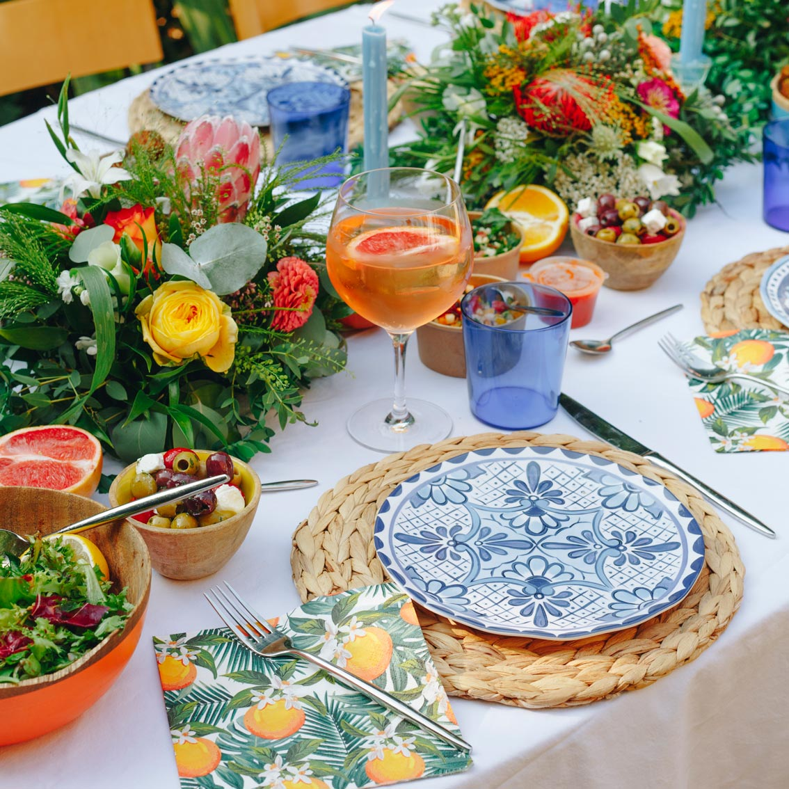 Sarah's Mediterranean Table with Blue and White Plates, Orange Botanical Paper Napkins and Beautiful Table Flowers Centrepiece - Talking Tables UK