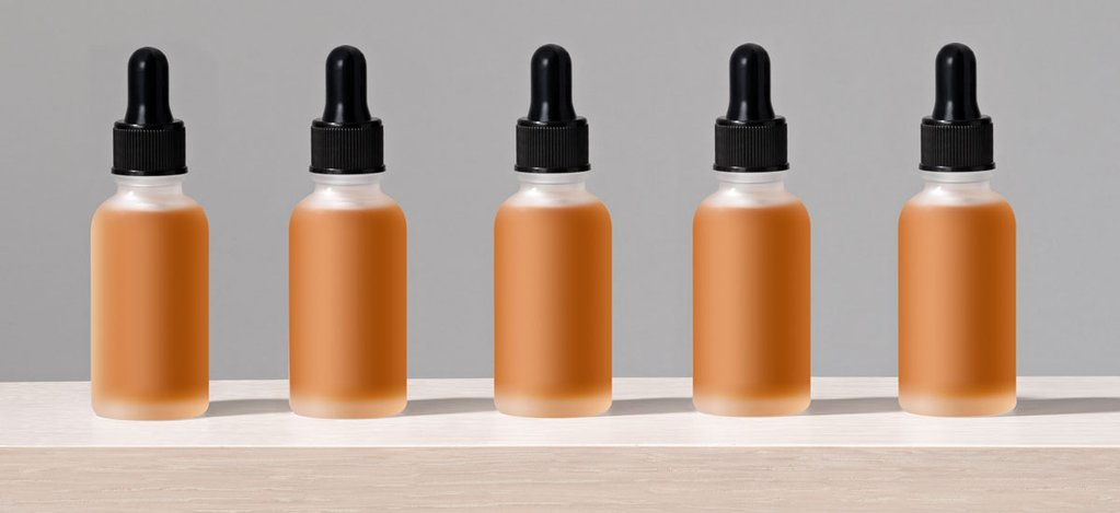 Five small glass bottles with CBD