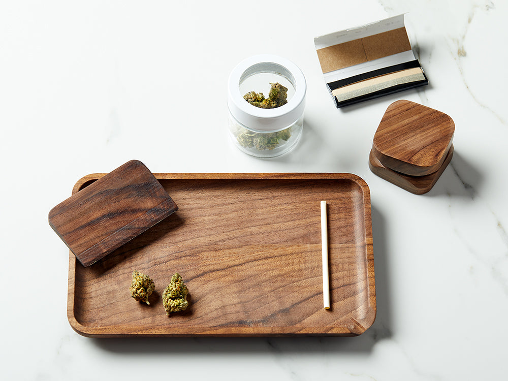Image of a rolling tray and rolling accessories with dried cannabis