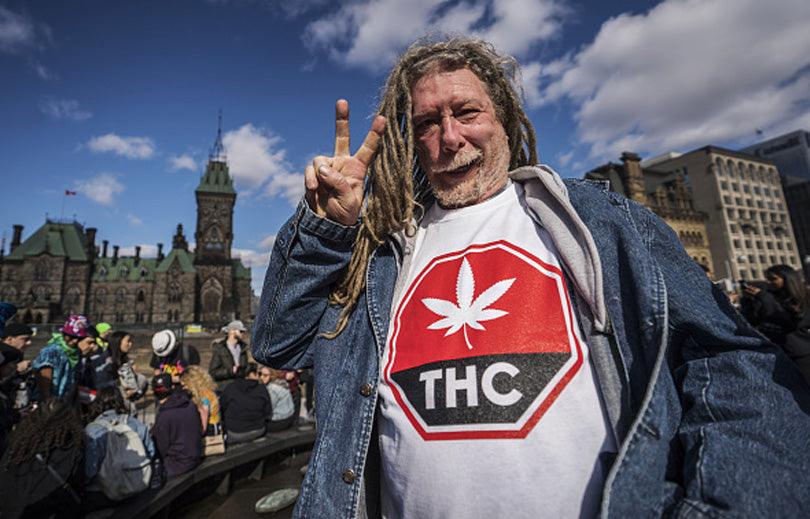 Image of a man wearing a THC T-shirt standing in front of parliament hill.