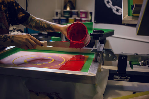 A bucket of red ink being poured onto a screen