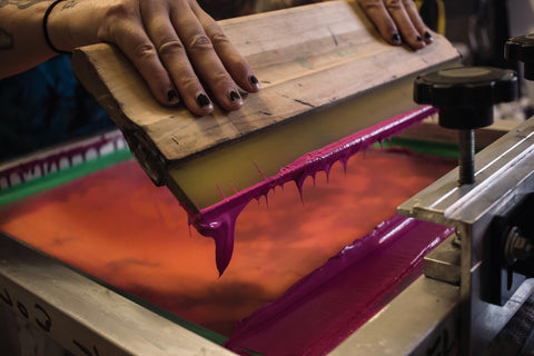 Two hands hold a squeegee with magenta ink