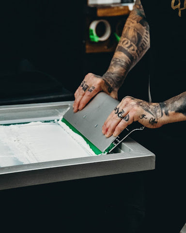 Two hands push a squeegee on a screen of white ink