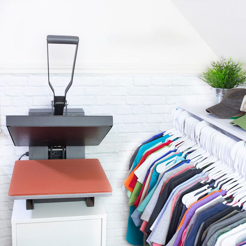 A heat press sits next to a rack of colorful shirts