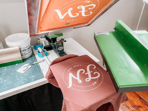 """A shirt with the letters """"FN"""" on a press with a flash dryer to the right"""