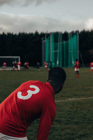 A man wears a red jersey with the number 3