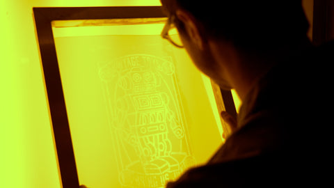 A man with glasses looks at a screen with a design under yellow light