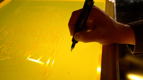 A hand holds a blockout pen and draws over pinholes in a screen