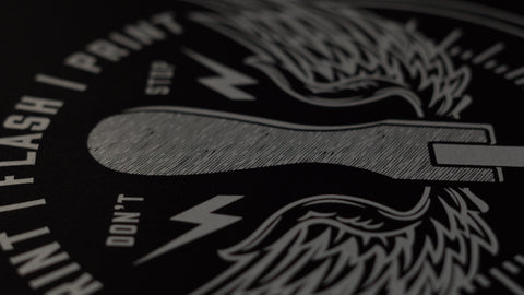 a close up of a white plastisol ink print on a black shirt
