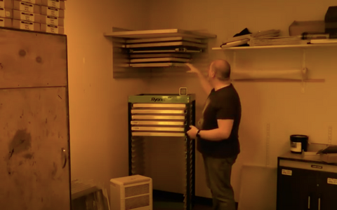 person in a dark room showing screen racks