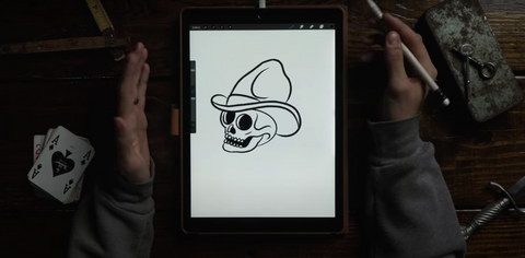 hands drawing a skull on an ipad