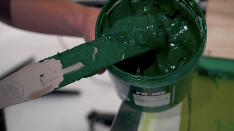 hand scooping out green plastisol ink