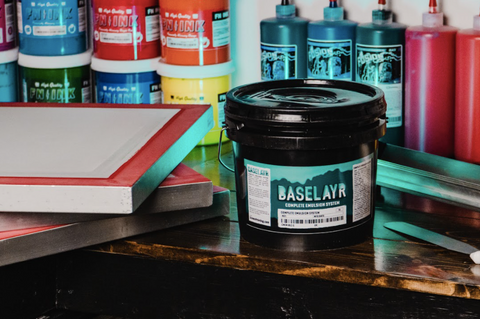 baselayr complete emulsion on a table next to a few screens with inks behind it