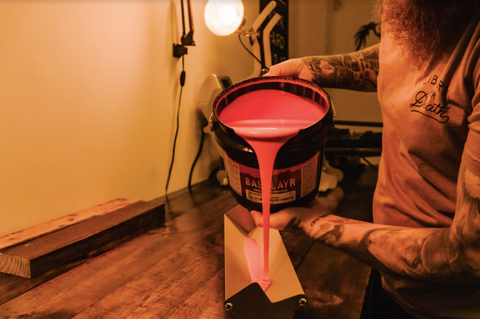 person pouring emulsion into a scoop coater