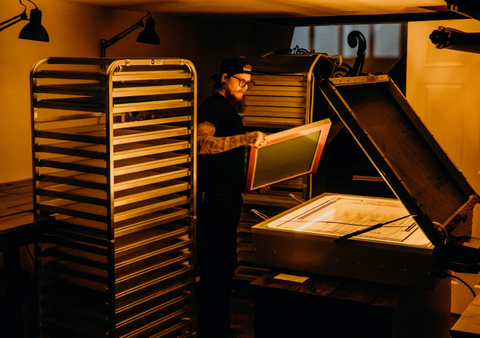 A man inspecting a screen in a darkroom