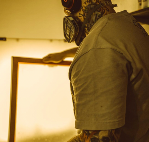 A man wearing a respirator holding a screen