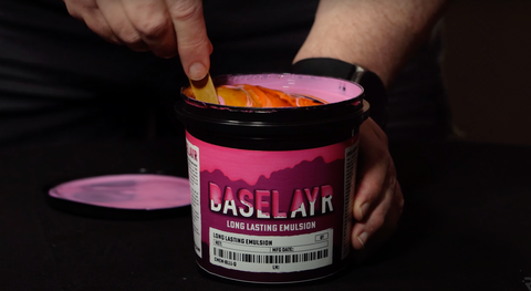 A hand mixing diazo into pink emulsion