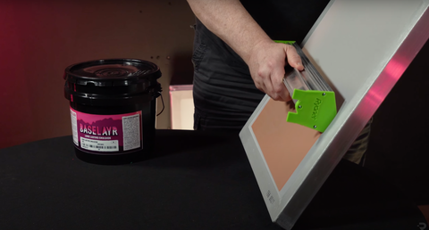 A hand holding a scoop coater of emulsion to a screen
