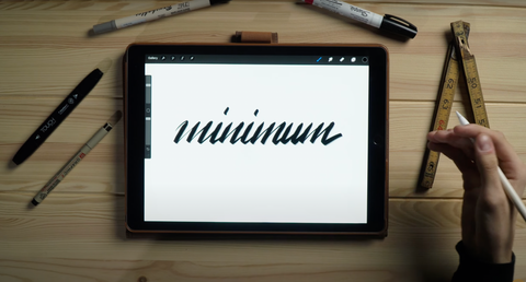 """A hand rests next to the calligraphy word """"Minimum"""""""