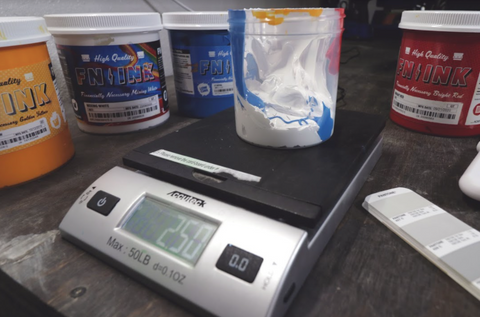 a scale with a container on it with white and blue ink in it. yellow, mixing white, blue, and red ink around it