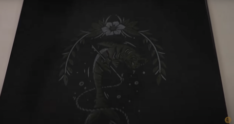 A faded image of a tiger/shark mashup on a black piece of paper