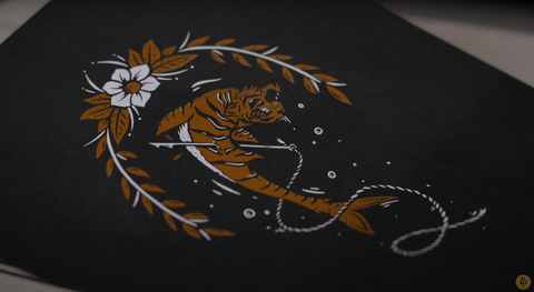 A crisp image of an orange shark with a tiger head and white flower on black paper