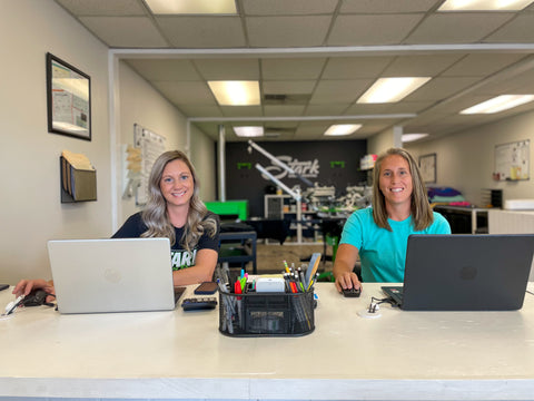 Daniela Murphy and Amy DiVernieri sit at a table with open laptops