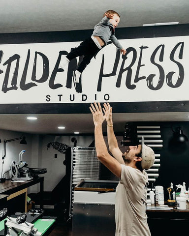 Cory tossing his son in the air at the studio