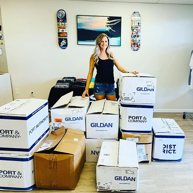 woman standing behind a ton of boxes