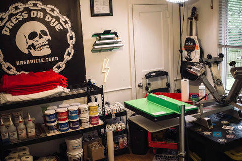 A screen printing shop with a flash dryer, ink, and skull poster