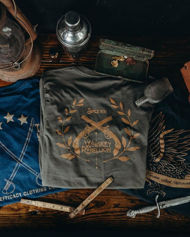 three shirts on a table with a few daggers, lamp, and sticks