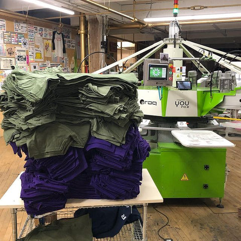 a stack of shirts by a roq press
